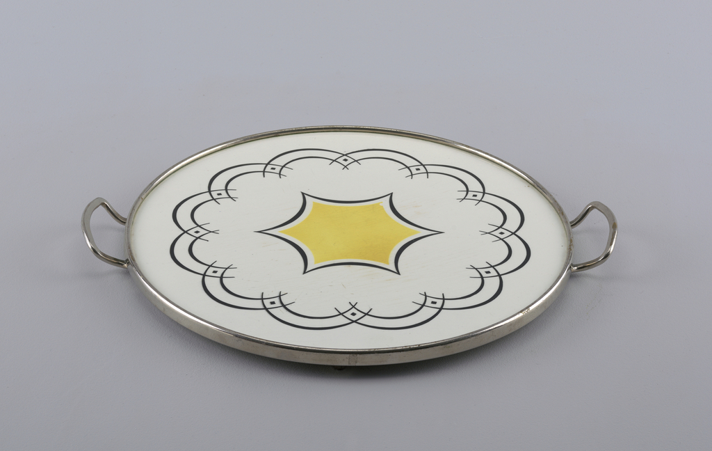 Circular flat plate with slightly raised edge and raised rim on bottom.  Yellowish-cream background glaze with black on edge.  Surface pattern divided into equal quarters by black airbrushed lines.  Each quarter contains two joined orange circles with black highlights.