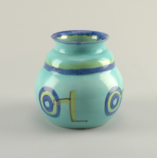 Bulbous bodied vase with more narrow shoulders and flared open mouth. Decorated with circles and geometric shapes in blue and yellow on light blue ground.