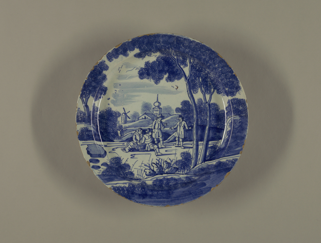 Circular plate with deep cavetto, standing on short foot rim; painted in underglaze blue on white with overall scene of 4 figures in landscape (two seated, two standing), 2 large trees on right, a windmill and onion-domed tower background, spongework leaves.