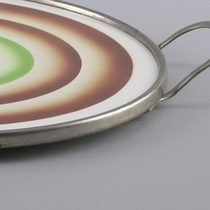 Flat round plate with concentric brown circles. At center a green ring with abstract forms. Simple metal rim and handle.
