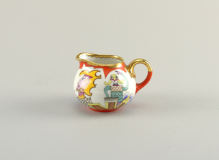 Bulbous creamer with loop handle. Gilt rim and handle. Body depicting abstract multicolored figures.