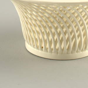 A flared white basket in a loose cross-hatched pattern in the style of wicker.