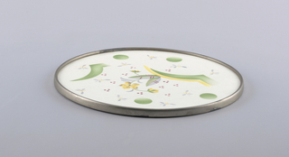 Flat circular tray with simple metal rim. White ground with scattered dots and stylized flowers.