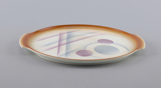 Circular plate with slightly raised edge.  White ground with four concentric airbrushed circles of alternating orange and blue.  Second orange line possesses four sets of airbrushed blue and orange semi-circles placed evenly on the line.  In the center sits a large white empty circle.