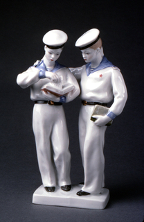 Two young boys dressed in sailors uniforms, one holds open book, the other holds book with left hand and rests right hand on shoulder of other boy; small rectangular base.