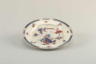 Flat marly, scalloped edge. Underglaze cobalt blue decoration, overglaze red enamel and gilding. Scattered single flowers and sprays of flowers and foliage.