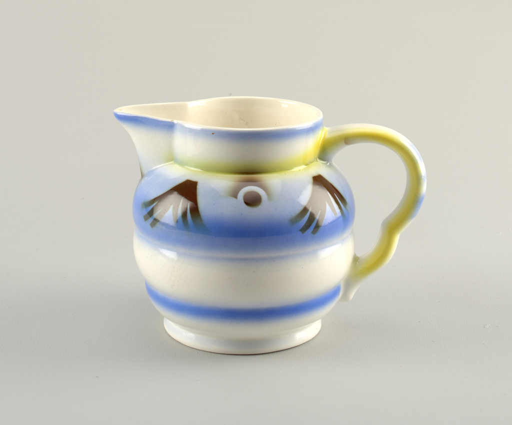 Blue glazed horizontal stripes on the broadly ribbed body. Yellow glaze on ear-shaped handle.