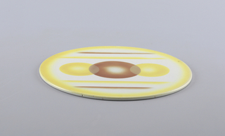 Flat circular tray decorated with three overlapping circles in yellow and orange-brown. Atomized yellow glaze at rim.