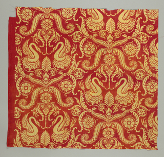 Fragment of cotton, close tabby weave, bright red background, design in yellow, printed (roller or plate?), drop repeat. Design of symmetrical arrangement, late classic influence. Shows confronted swans with pearls in beaks; below and above, palmette, foliage, rosettes, etc. Fragment shows two repeats scross, third interrupted. Right selvage present.