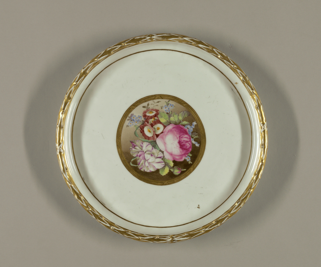 Circular; raised rim decorated in relief with laurel band, gilded.  Central medallion of flowers, polychrome, surrounded by gilded band.  Bottom unglazed.