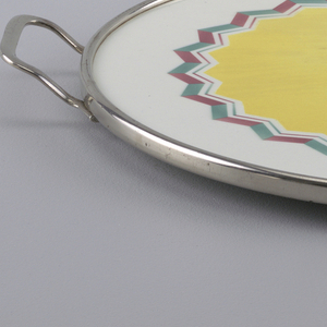 Flat circular tray decorated with large central star framed in green and pink. Simple rim and handles.