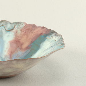 Very thin red clay and hand formed. Funnel-shaped with small flat base; edges sharp, irregularly crimped and irregular in outline. Base is glazed but uncolored. Variegated colored glaze applied in splotches and wide drips.