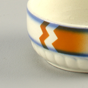 Round with molded gadrooning at bottom. Smooth upper band decorated with abstract orange and blue glaze on creamy white ground.