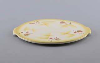Flat circular tray with two small protruding handles. White ground glaze with geometric pattern in yellow with orange circles.