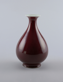 Broad pear-shape, with trumpet lip. Coated from white rim to low foot with monochrome glaze having pear skin texture.