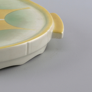 Circular plate with molded top edge and a recessed base with scalloped bottom edge.  Two yellow rectangular tab handles placed across from each other.  White background with yellow edge and airbrushed design of a scalloped and spiked star-like form bordered in green with a green and white center and yellow semi-circles leading to outer spikes.