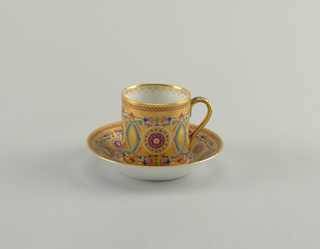 An cylindical orange porcelain cup with white interior. The cup has border around the top and a detailed circular pattern in the middle with a flower in the center of the circular forms.
