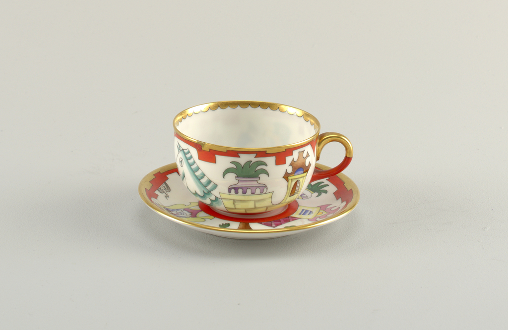 Cup and saucer decorated with gold rim and a frieze of comical stylized characters; figures in a boat, a castle, a potted plant, and a horse, among others.