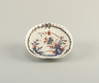 Scalloped shell form with Chinese-style decoration and bow knot.