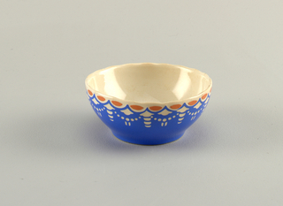 Deep circular bowl with scalloped edge. Surface of interior and exterior glazed white.  Exterior covered with royal blue. Near top blue and white contrast to form a pattern of beaded chains interspersed with arrows and lines.  At the very top, above connected blue semi-circles, sit irregularly shaped, evenly spaced orange ovals.