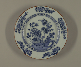 Circular plate with wide rim; painted in underglaze blue on white, center with chinoiserie scene of pavillion in landscape, cavetto with diaper pattern, outer rim with dot and line border.
