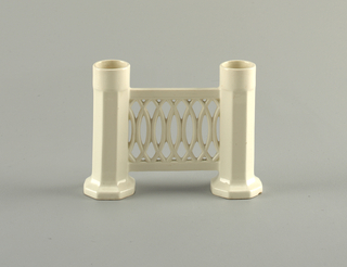Two columns, open at top and on hexagonal base. Pierced connecting band. Cream glaze.