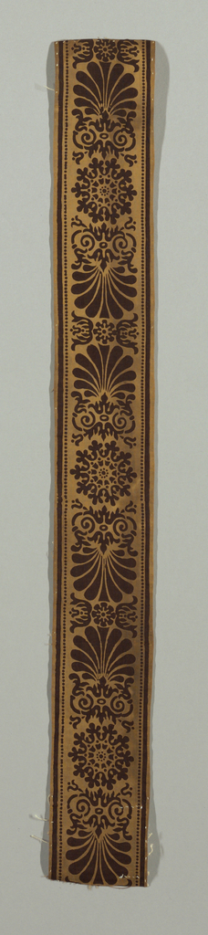 Border with curving and shell-like shapes in brown on a dark yellow ground.