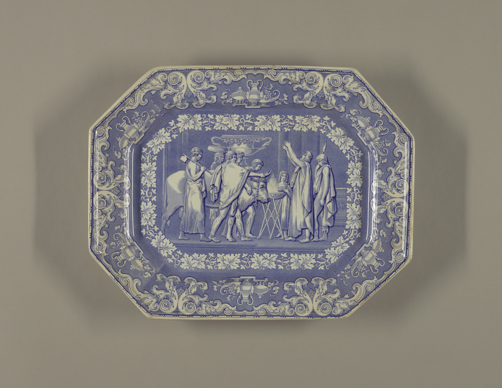 Rectangular tray with angled corners and blue transfer print showing a classical scene of sacrifice. Scrollwork border with pottery and grape vines.