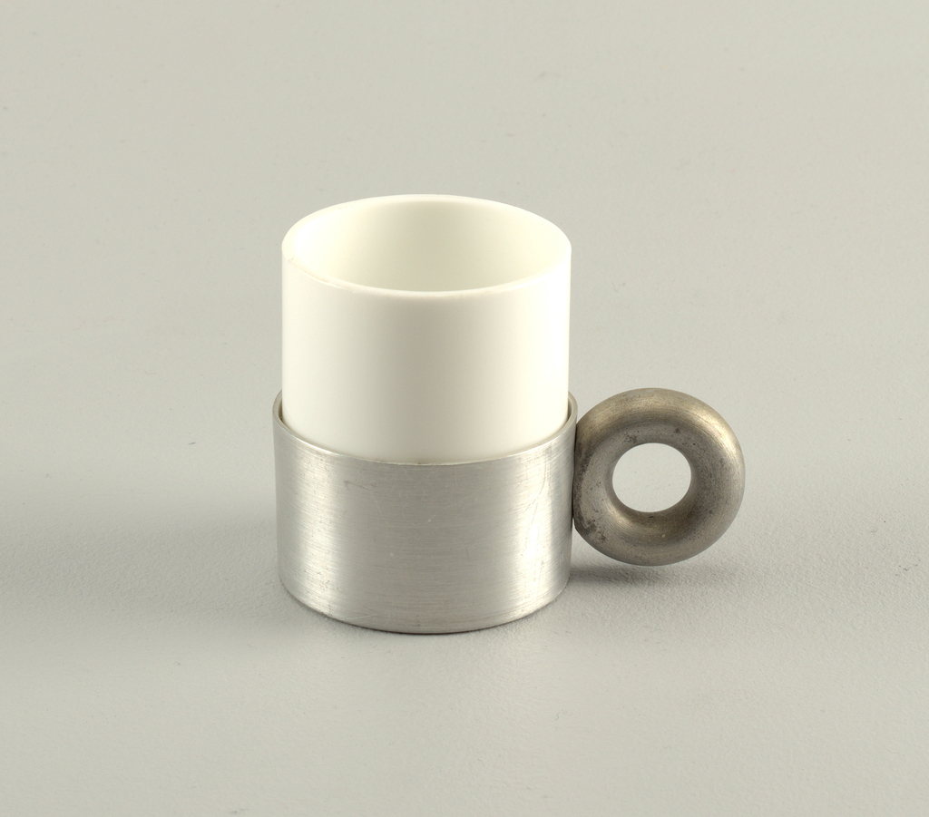 White cylindrical porcelain cup (a) in short cylindrical aluminum holder (b) with thick circular handle.