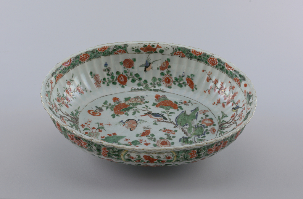 Fluted oval formed dish, famille verte, decorated on the rim  and sides with bands of green foliage and iron red flowers, the outside band interrupted by cartouches of carp, the basin decorated with birds, prunus, flowers and foliage.