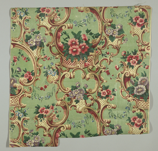 Flowers in polychrome and elaborate scrollwork in tan and red on a green ground.
