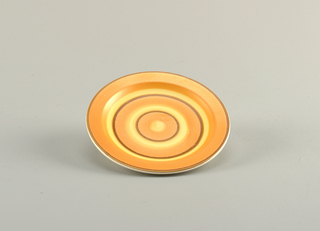 Round plate with concentric rings in orange, yellow and brown glaze.
