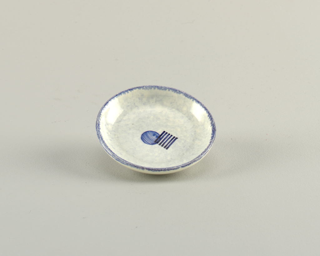 Round dish with a blue rim and decorated with a solid blue circle in the center with 6 short black stripes