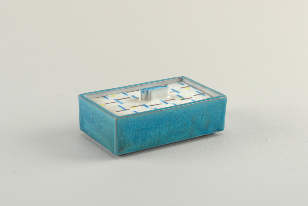 Rectangular box with blue glaze. Flat, sunken lid with geometric pattern of lines in primary colors.