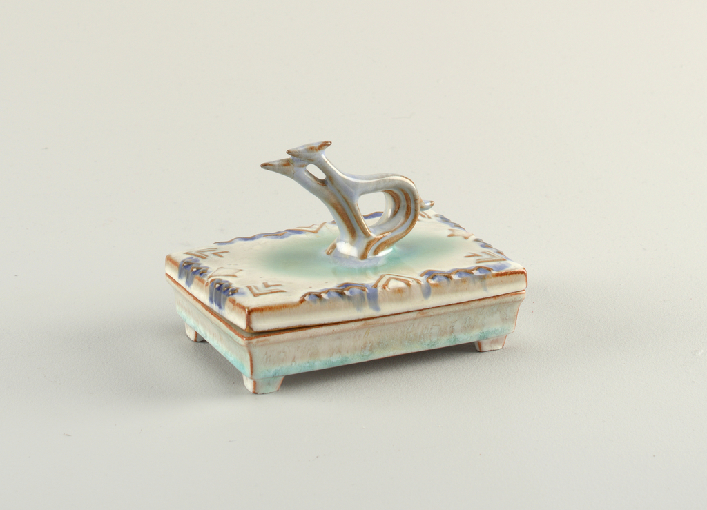 Low rectangular box with flat lid molded with arrowhead pattern. Stylized double gazelle finial. Liquid glaze showing colour of clay on high points.