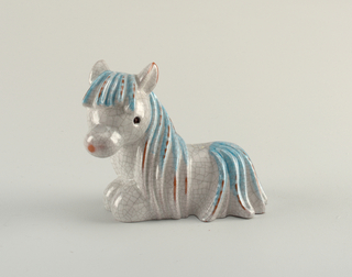Recumbent pony with blue mane.  Grey glaze with crazing.