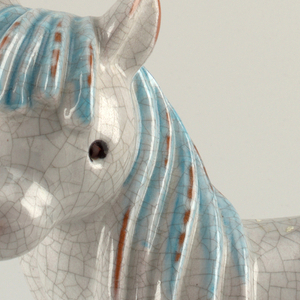 Recumbent pony with blue mane.  Grey glaze with crazing.