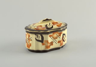 Faceted box and domed lid with ridged handle. Abstract decoration in orange and black on pale yellow ground. Black atomized glaze at edges.