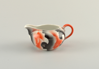 Creamer with atomized red and black glaze in amorphous design on a white ground.