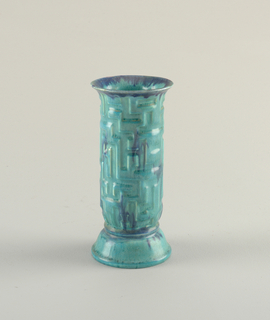 Basic cylindrical form with flaring mouth and rounded flaring foot.  The molded articulated surface glazed in mottled aqua and blue.