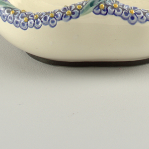 Oval basket with broadly pointed walls that swell into the handle. Creamy glaze with purple and yellow floral pattern along handle and rim.