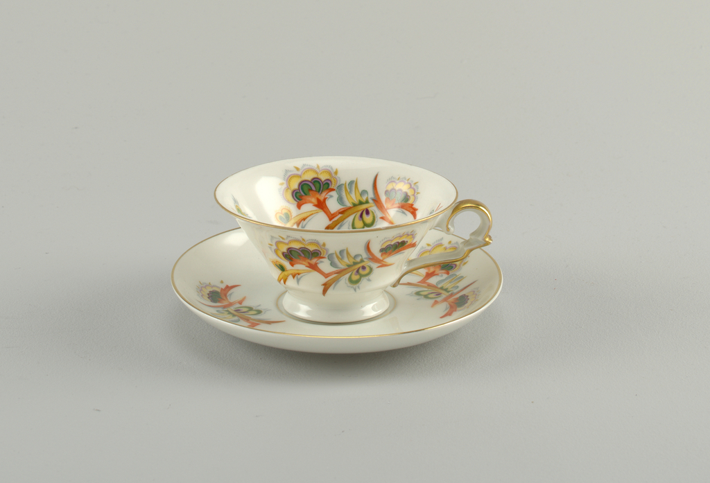 Tulip-shaped round cup with offset circular base and scrolling heart-shaped handle.  White background with gold lining the top edge and the handle.  Interior and exterior symmetrically decorated with flame-like flowers in yellow, tan, green, red, purple, and gray.  Circular saucer with raised bottom rim.  Saucer also with white ground color and gold lining the top edge, and a gold circular line around the center.  Between these two lines sit flowers, symmetrically placed that match the tea cup.