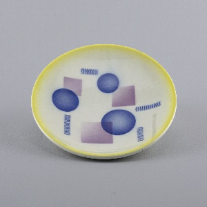 Circular form with upraised rim glazed in yellow; geometric decoration of overlapping circles and squares with bands of wavy lines, in blue and violet, scattered on white ground.