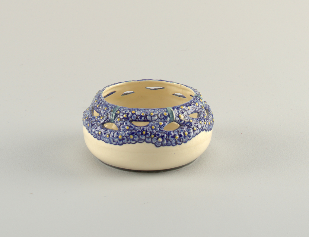 Squat globular form, the upper section molded with pierced band of petalled flowers in underglaze blue with yellow centers. White ground on exterior and interior.