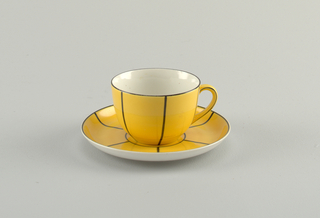 Circular cup with heart-shaped handle.  Yellow ground on the exterior with regularly spaced black lines on the body.  Black lines also on handle and the top rim.  Circular concave saucer with a raised bottom rim.  Also a yellow ground on the top surface with black circular lines from the center and six radiating black lines stretching out to the another black line on the edge.