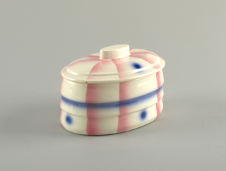 Ovoid body molded with vertical ridges; oval stepped lid with tab handle.  White ground decorated with airbrushed pink lines radiating from center, blue dots and  one blue horizontal band.