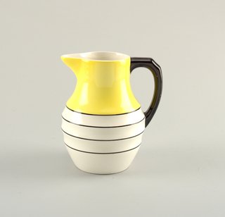Bottom of pitcher is white with black ribs. Upper portion is smooth and yellow. Black handle.