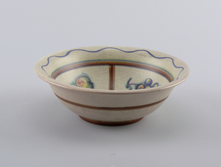 Circular bowl with raised bottom rim and outward curving top edge.  Tan crackle-glazed ground.  On exterior, a line of brown on the bottom rim and in the middle around the bowl.  On the interior, a wavy line of blue at the top with a central circular design of four quadrants broken up by brown lines containing different fruits.  Quadrants bordered by green, blue, brown, and blue lines.  In the very center a small circle constructed by lines of green, blue, brown, and blue.