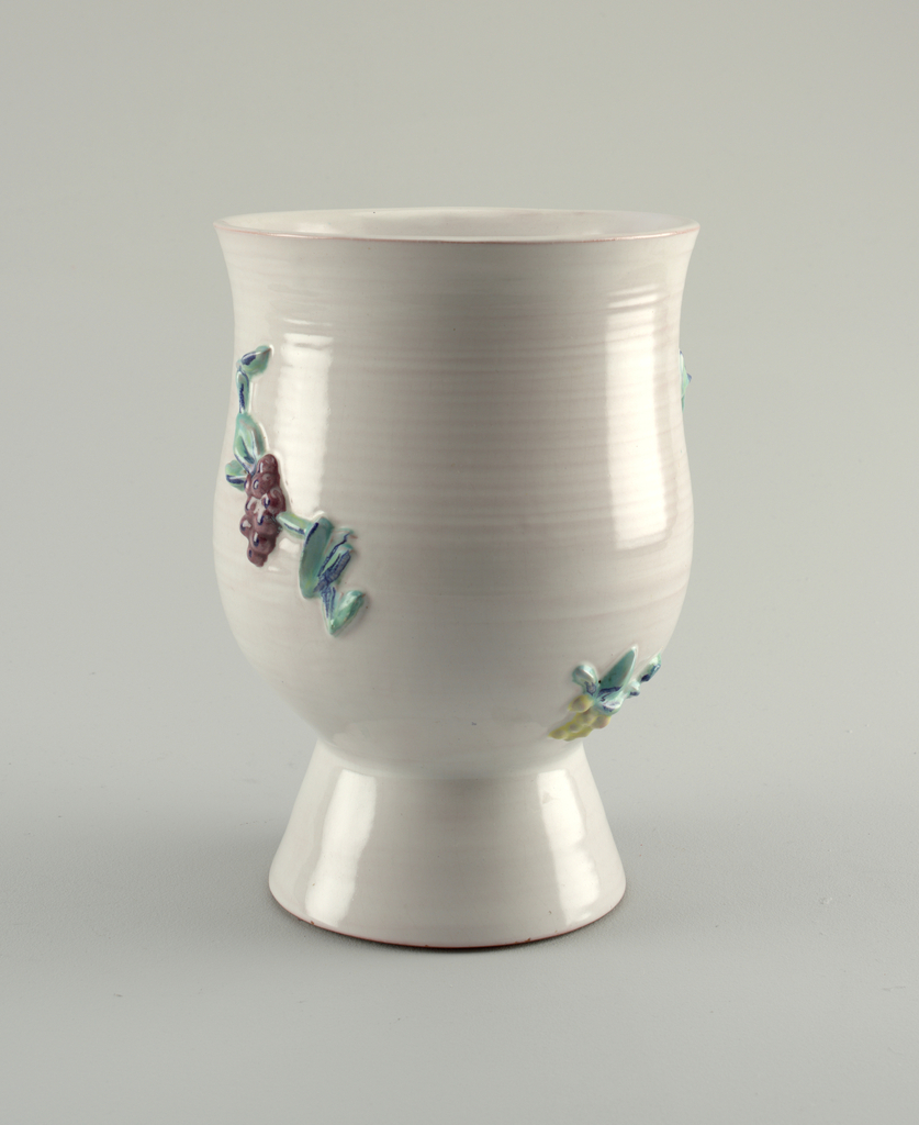 Goblet with flaring rim on a high tapering foot. Visible throwing marks. Applied floral decoration.