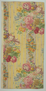Polychrome block print on yellow linen. Large cluster of flowers in pink, blue, yellow, purple and red with green leaves. These clusters in off-set rows are attached to a vertical band of grey-lace -like ribbon trimmed with a blue and yellow ribbon and yellow-red flowers. Spaced in background are grey stripes of ribbon with purple jewels.